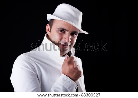 smiling man with his white hat and coat, isolated on black. Studio shot - stock photo