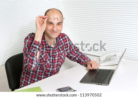 smiling man with laptop in office
