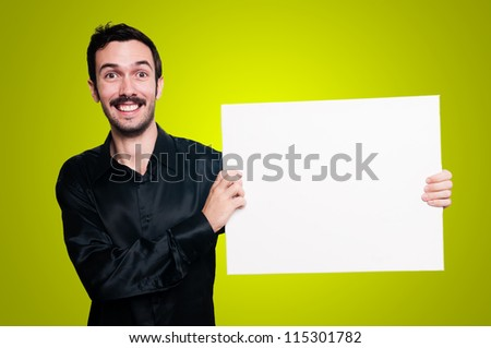 smiling man with mustache and black jacket holding blank white board on yellow background