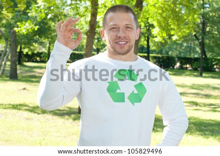 Smiling man with recycle logo on his shirt making OK gesture