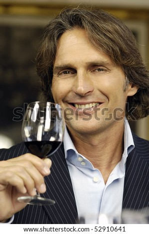 Smiling man with red wine - stock photo