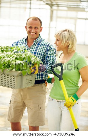 Smiling man with tray of plants and woman near by