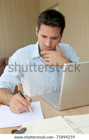 Smiling man working at home on laptop computer