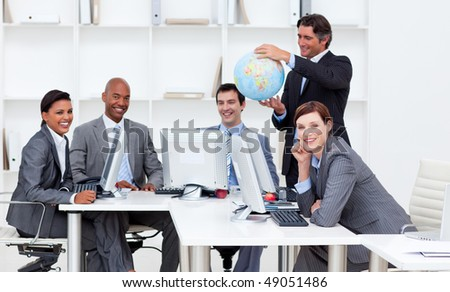 Smiling manager holding a terrestrial globe with his team working at computers. Business concept. - stock photo