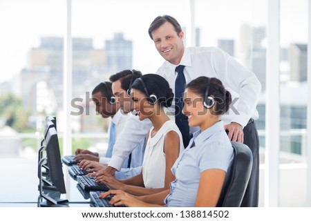 Smiling manager looking at camera while call centre employees working on computers - stock photo