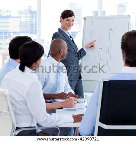 Smiling manager reporting sales figures to her team at a meeting - stock photo