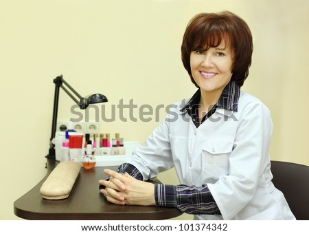 Smiling manicurist dressed in white robe sits at table for manicure in beauty salon