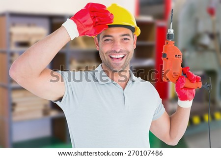 Smiling manual worker holding drill machine against workshop - stock photo
