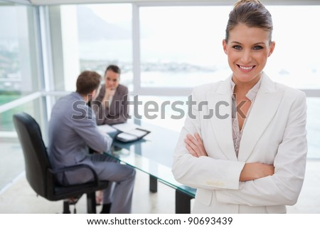 Smiling marketing manager standing in conference room with team sitting behind her