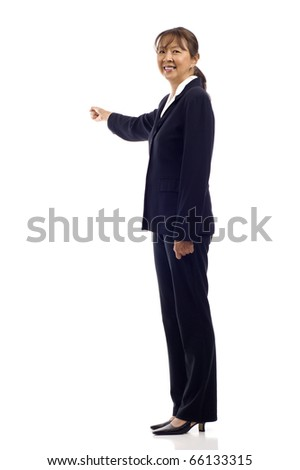 Smiling mature Asian business woman pointing at something over white - stock photo