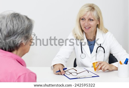 Smiling mature blond haired doctor sitting at the desk and talking with senior female patient. - stock photo
