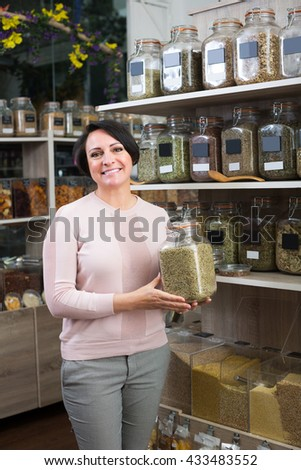 Smiling mature brunette woman choosing dried herbs sold by weight in organic shop