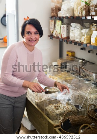 Smiling mature brunette woman 40s choosing cereals sold by weight in organic shop - stock photo