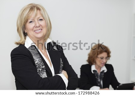 Smiling mature business woman with arms crossed looking at camera. - stock photo