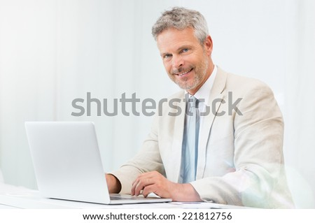 Smiling Mature Businessman In His Office Looking At Camera