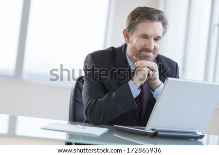 Smiling mature businessman with hands on chin looking at laptop in office