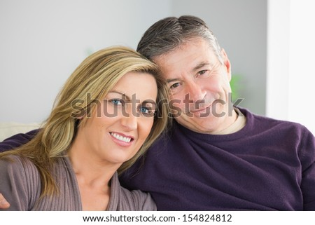 Smiling mature couple looking at camera in a living room - stock photo