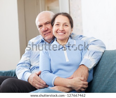 Smiling  mature couple on sofa in home - stock photo