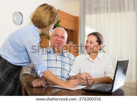 Smiling mature couple 60s years old discussing employee of  company at home - stock photo
