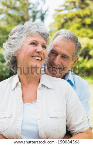 Smiling mature couple together in park embracing and laughing - stock photo