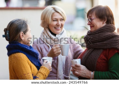 Smiling mature female in warm clothes having cup of hot tea on terrace