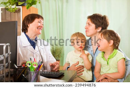 Smiling mature female pediatrician doctor examining children in clinic  - stock photo