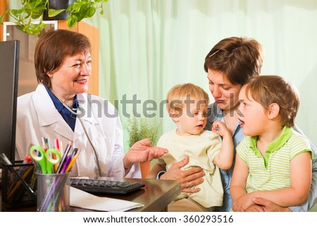 Smiling mature female pediatrician doctor examining two kids in clinic - stock photo