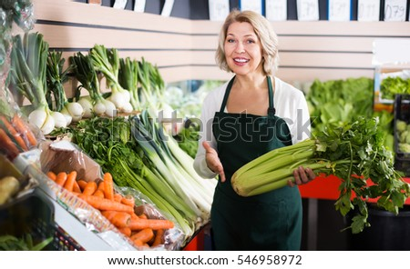 Smiling mature female seller posing with celery, parsley and leek