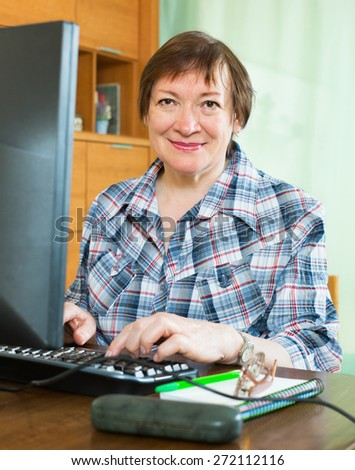Smiling mature female sitting in front of PC and using keyboard - stock photo
