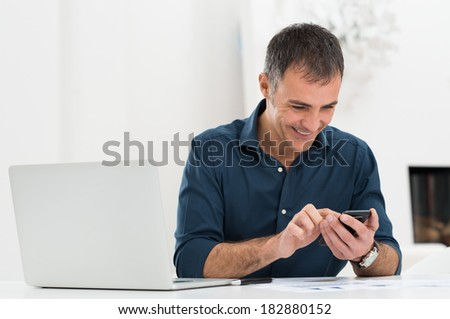 Smiling Mature Man In Front Of Laptop Using Cellphone - stock photo