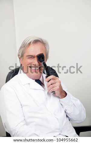 Smiling mature optometrist with ophthalmoscope for an easy view at retina - stock photo