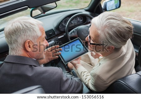 Smiling mature partners working together on tablet in classy car on a bright day - stock photo