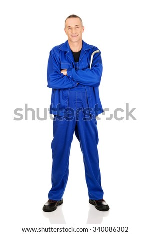 Smiling mature repairman holding wrench.