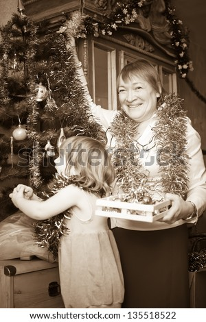 Smiling mature woman and child preparing for  Christmas. Imitation of an old photo