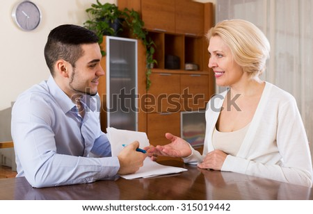 Smiling mature woman and young fiance signing marriage settlement