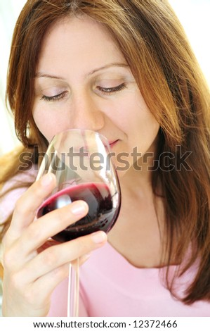 Smiling mature woman holding a glass of red wine - stock photo