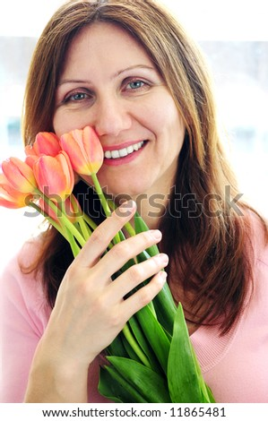 Smiling mature woman holding bouquet of flowers - stock photo