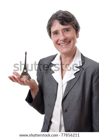 Smiling mature woman showing tiny eiffel tower in her hand isolated on white background - stock photo