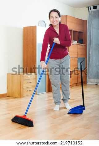Smiling mature woman sweeping the floor in living room - stock photo