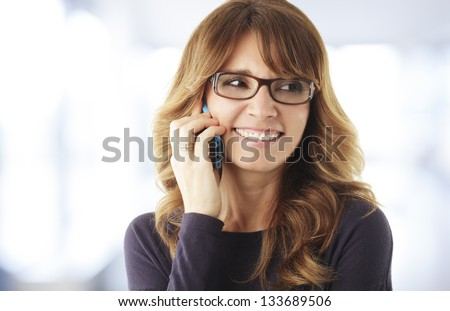 Smiling mature woman talking on phone in office