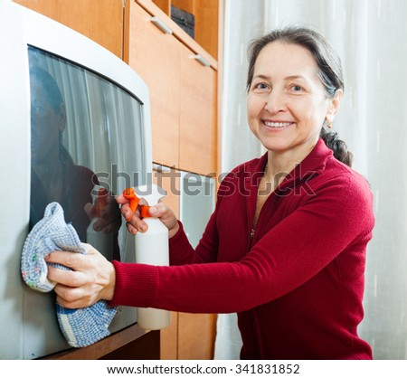 Smiling mature woman wiping the dust  on TV at home - stock photo