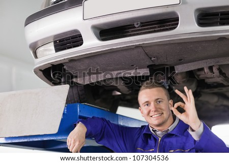 Smiling mechanic doing a gesture with his hand in a garage - stock photo
