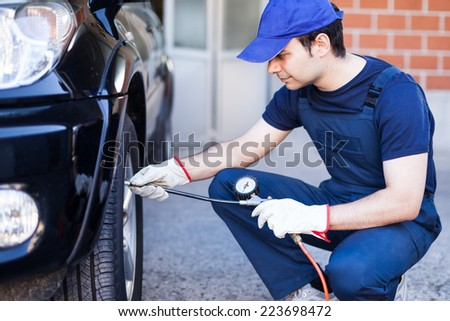Smiling mechanic inflating a tire - stock photo