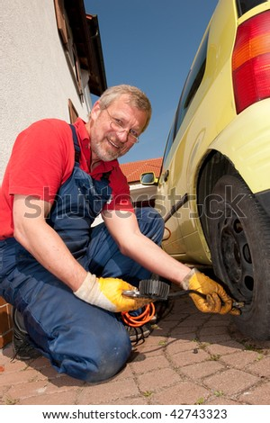 Smiling mechanic is checking the tire pressure - stock photo