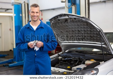 Smiling mechanic looking at camera at the repair garage