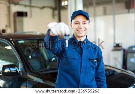 Smiling mechanic returning the keys to you - stock photo