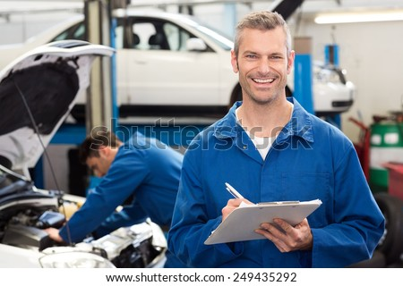 Smiling mechanic writing on clipboard at the repair garage - stock photo