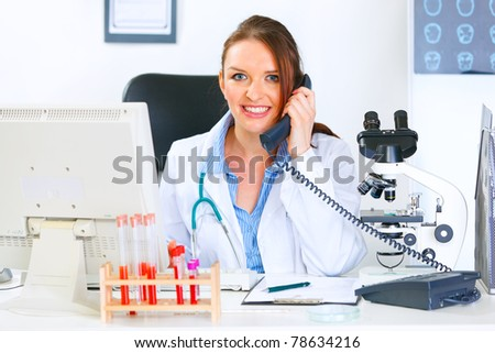 Smiling medical doctor woman sitting at office table and talking on phone - stock photo
