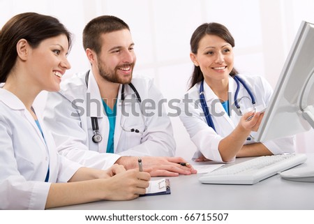 Smiling medical doctors talk on a workplace - stock photo