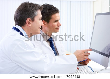 Smiling medical doctors with stethoscopes and computer. - stock photo